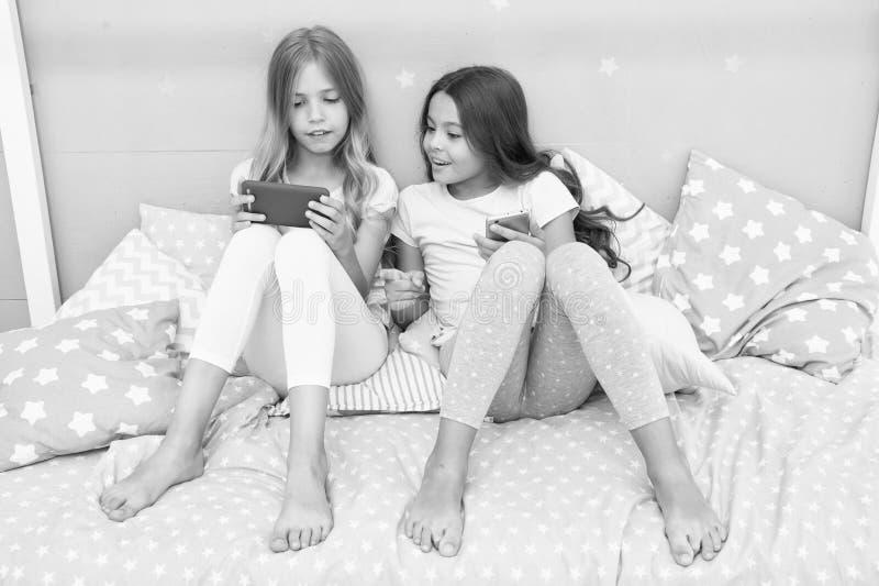 Οι αδελφές κοριτσιών φορούν την πυτζάμα πολυάσχολη με τα smartphones Τα παιδιά στην πυτζάμα αλληλεπιδρούν με τα smartphones Εφαρμ στοκ φωτογραφίες
