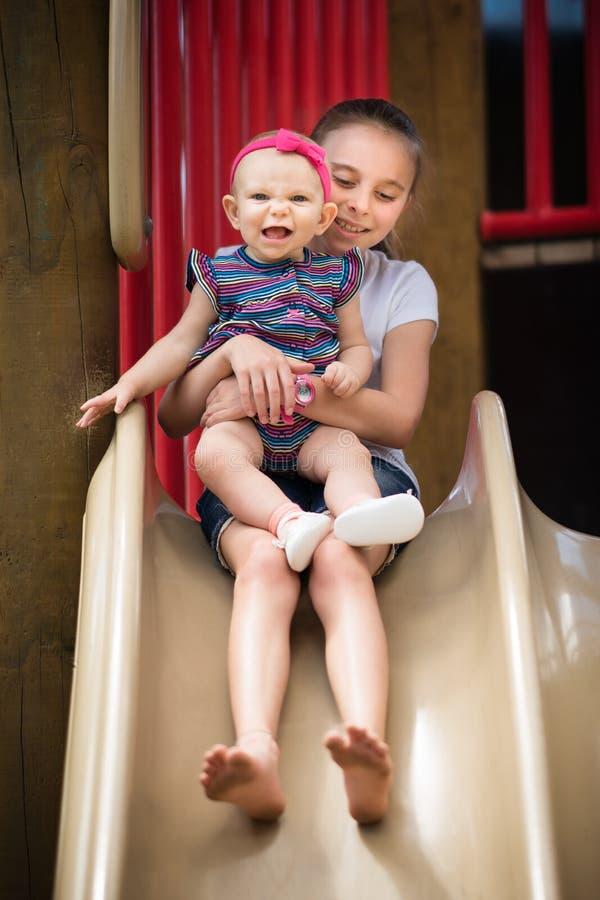 Οι αδελφές στην παιδική χαρά γλιστρούν στοκ φωτογραφία με δικαίωμα ελεύθερης χρήσης