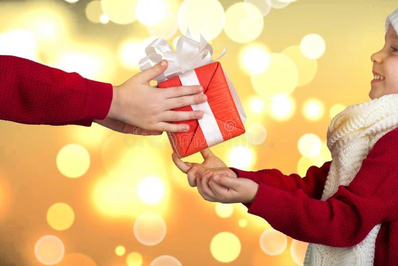 Οι αδελφοί ανταλλάσσουν τα δώρα Χριστουγέννων Τα χέρια των παιδιών με ένα δώρο Χαρούμενα Χριστούγεννα και καλές διακοπές! στοκ φωτογραφία