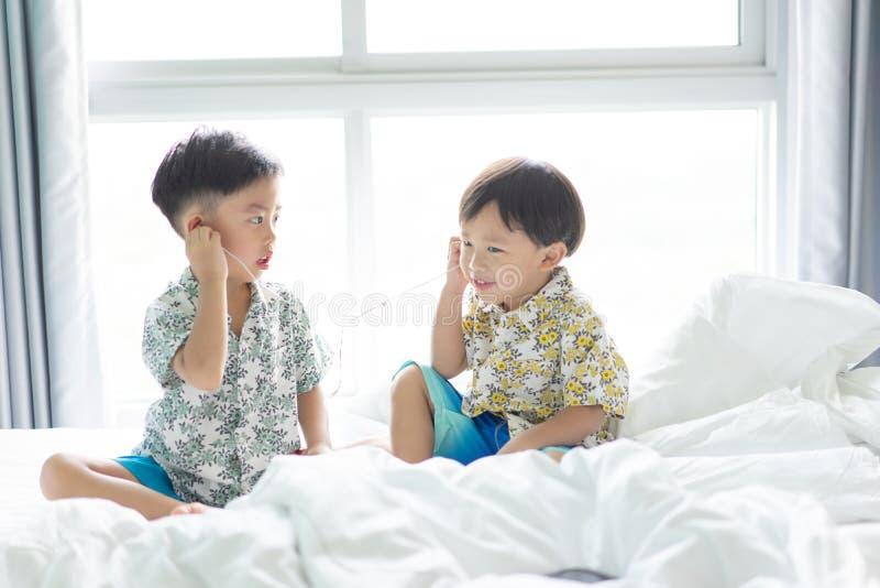 Οι αδελφοί είναι ακούοντας το τραγούδι με το τηλέφωνο κυττάρων το πρωί στοκ εικόνες με δικαίωμα ελεύθερης χρήσης