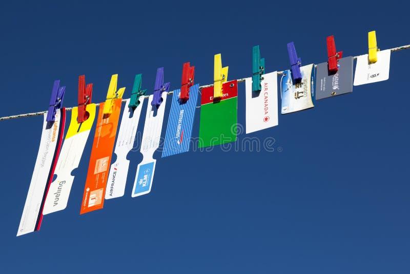Οι αερογραμμές δίνουν τις ετικέττες αποσκευών που κρεμούν από το clothespin στο μπλε στοκ εικόνες με δικαίωμα ελεύθερης χρήσης
