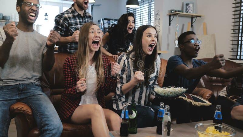 Οι αθλητικοί θαυμαστές αφροαμερικάνων γιορτάζουν κερδίζουν στο σπίτι Οι εμπαθείς υποστηρικτές φωνάζουν παιχνίδι προσοχής στη TV 4 στοκ φωτογραφίες