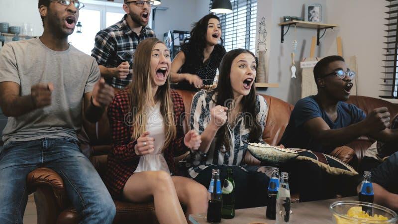 Οι αθλητικοί θαυμαστές αφροαμερικάνων γιορτάζουν κερδίζουν στο σπίτι Οι εμπαθείς υποστηρικτές φωνάζουν παιχνίδι προσοχής στη TV 4 στοκ εικόνες με δικαίωμα ελεύθερης χρήσης