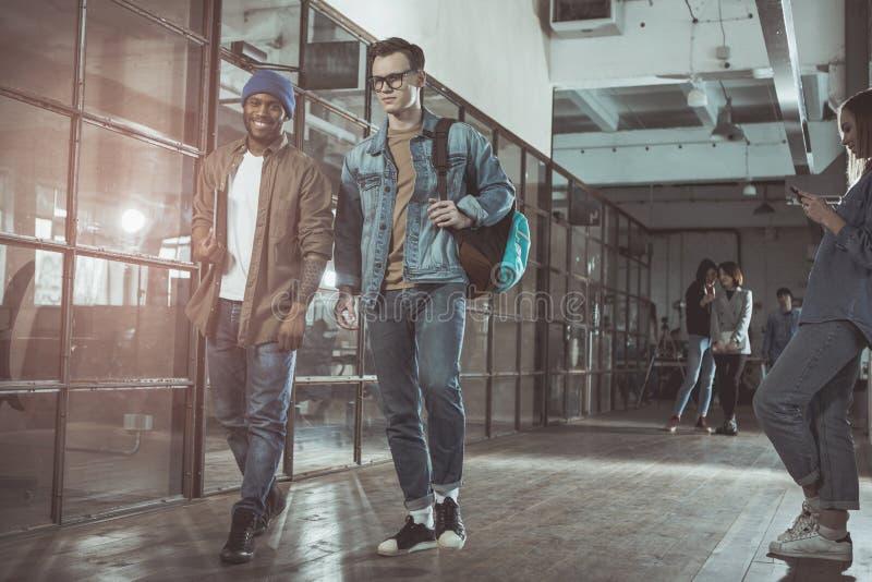 Οι αισιόδοξοι άνδρες συνάδελφοι ολοκληρώνουν την εργασία τους στοκ φωτογραφίες