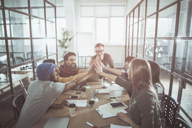 Οι αισιόδοξοι συνάδελφοι κρατούν τα χέρια από κοινού στοκ φωτογραφίες