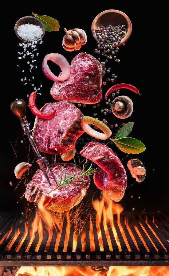 Οι ακατέργαστες μπριζόλες βόειου κρέατος με τα λαχανικά και τα καρυκεύματα πετούν πέρα από την καμμένος πυρκαγιά σχαρών σχαρών στοκ φωτογραφίες