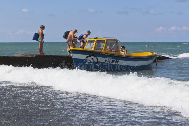 Οι ακραίοι προσγειωμένος άνθρωποι με τον υγρό κυματοθραύστη στην παραλία στην τακτοποίηση θερέτρου Adler motorboat για τη θάλασσα στοκ εικόνα με δικαίωμα ελεύθερης χρήσης