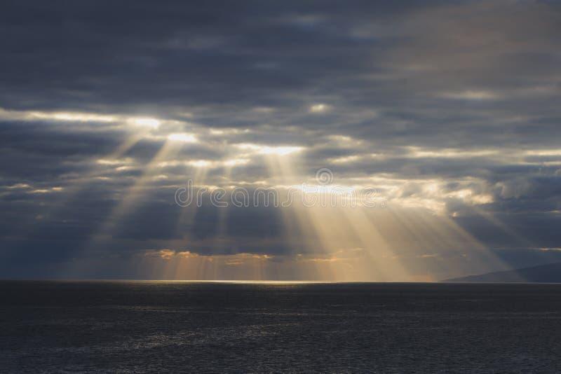 Οι ακτίνες ήλιων λάμπουν μέσω των σύννεφων στοκ φωτογραφίες