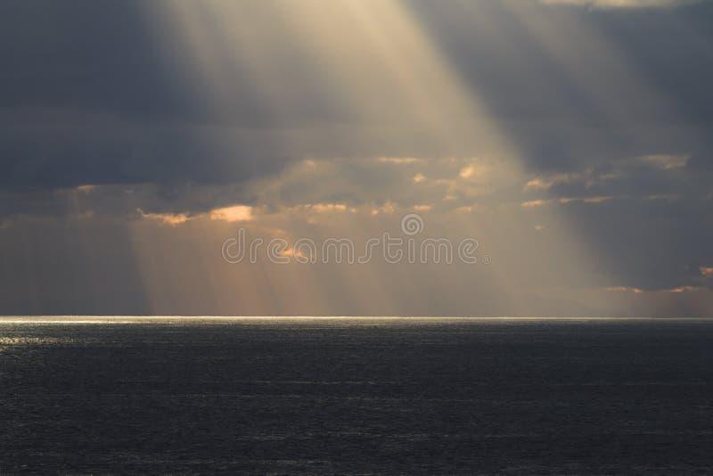 Οι ακτίνες ήλιων λάμπουν μέσω των σύννεφων στοκ φωτογραφία