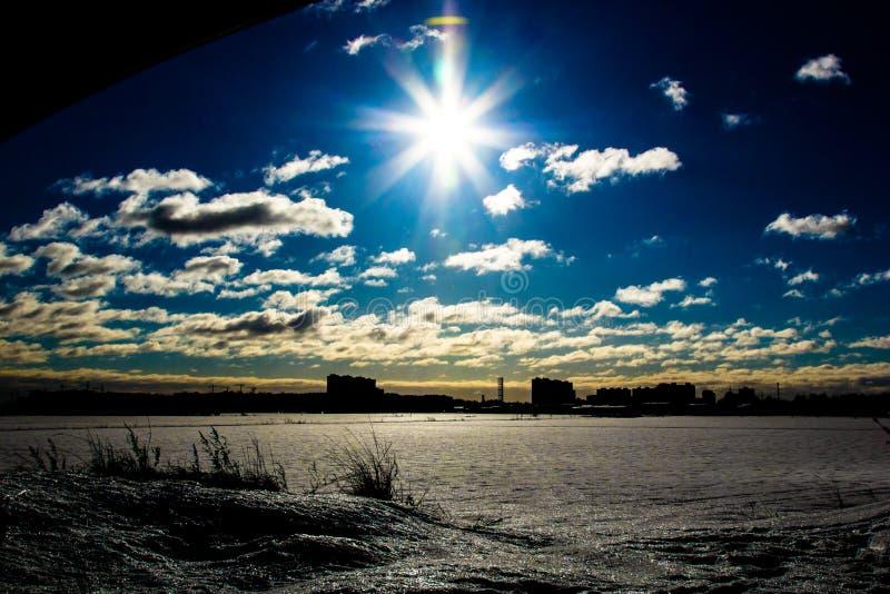 Οι ακτίνες του ελαφριού, φωτεινού ήλιου πέρα από τη χιονώδη πεδιάδα με την ξηρά χλόη στο μέτωπο, η σκιαγραφία μιας απόμακρης πόλη στοκ φωτογραφία με δικαίωμα ελεύθερης χρήσης
