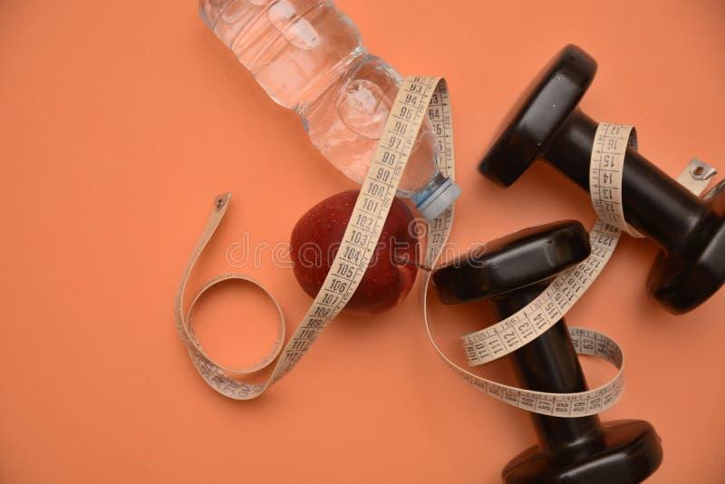 Οι αλτήρες ποτίζουν την ικανότητα διατροφής μετρητών μέτρου μήλων υγείας και το wellness σωμάτων ομορφιάς ενεργειακού αθλητισμού  στοκ φωτογραφία με δικαίωμα ελεύθερης χρήσης