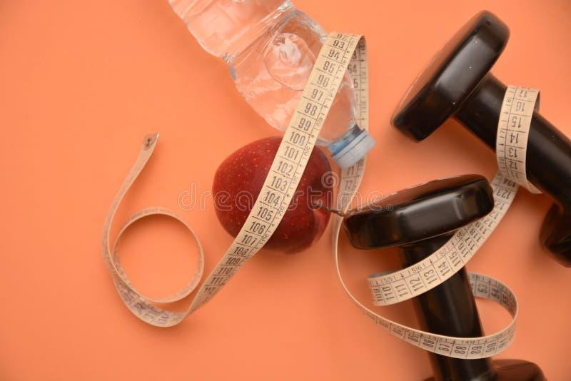 Οι αλτήρες ποτίζουν τον υγιή αθλητισμό σωμάτων ομορφιάς υγείας τροφίμων μήλων μετρητών μέτρου wellness διατροφής γυμναστικής ικαν στοκ φωτογραφία με δικαίωμα ελεύθερης χρήσης