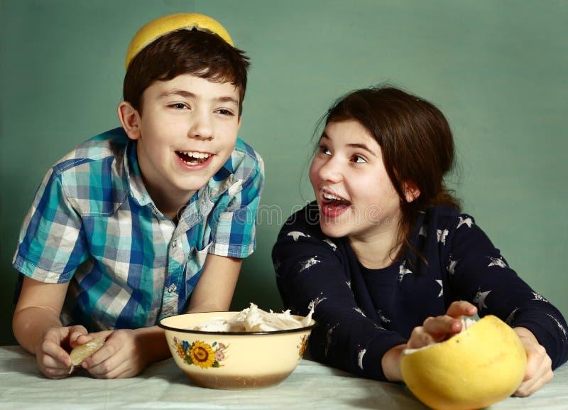 Οι αμφιθαλείς παιδιών που ξεφλουδίζουν τα φρούτα σταφυλιών κάνουν το αστείο καπέλο στοκ εικόνες με δικαίωμα ελεύθερης χρήσης