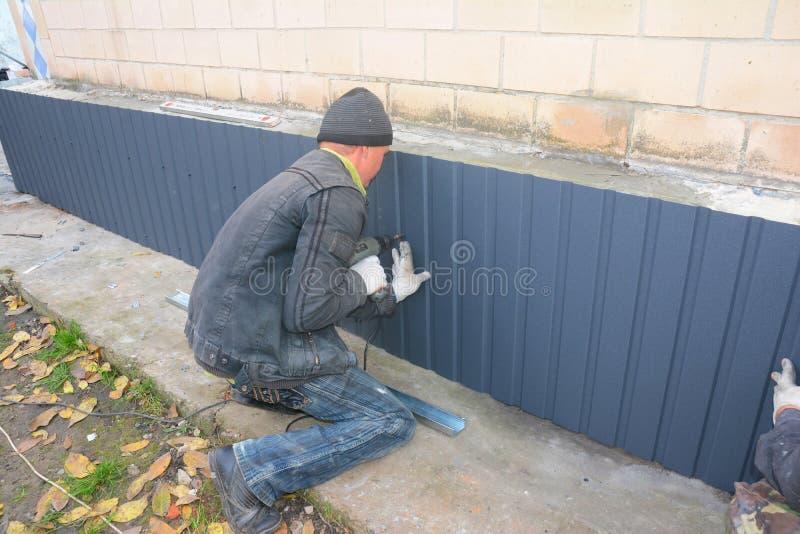 Οι ανάδοχοι κτηρίου με το ίδρυμα επισκευάζουν Επισκευή και ανακαίνιση τοίχων ιδρύματος με την εγκατάσταση των φύλλων μετάλλων για στοκ εικόνα