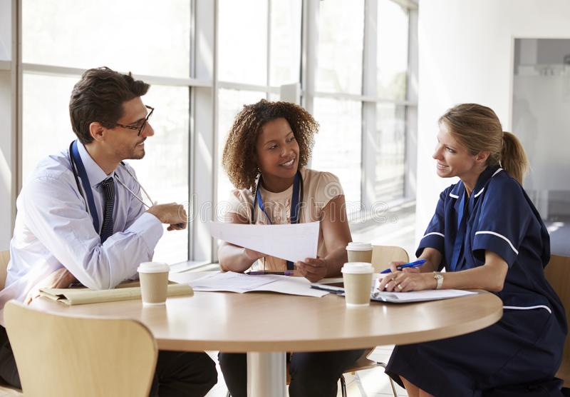 Οι ανώτερες διαβουλεύσεις υγειονομικής περίθαλψης σε μια αίθουσα συνεδριάσεων, κλείνουν επάνω στοκ εικόνα