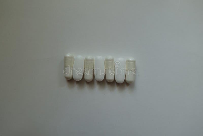 Οι απλές κάψες του κιτρικού άλατος μαγνήσιου και τα caplets του ασβεστίου citrate σε μια σειρά άνωθεν στοκ εικόνα με δικαίωμα ελεύθερης χρήσης