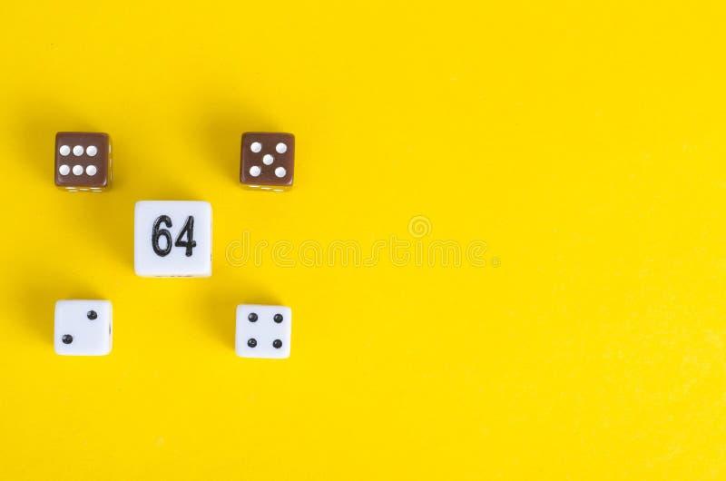 Οι απλοί κύβοι παιχνιδιών, χωρίζουν σε τετράγωνα στο φωτεινό κίτρινο υπόβαθρο Έννοια παιχνιδιού χαρτοπαικτικών λεσχών στοκ φωτογραφία