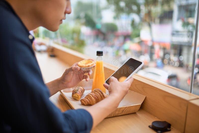 Οι αρσενικές αναζητήσεις χρειάστηκαν τις πληροφορίες μέσω του έξυπνου τηλεφώνου ενώ κάθεται στον καφέ πεζουλιών στοκ φωτογραφία με δικαίωμα ελεύθερης χρήσης