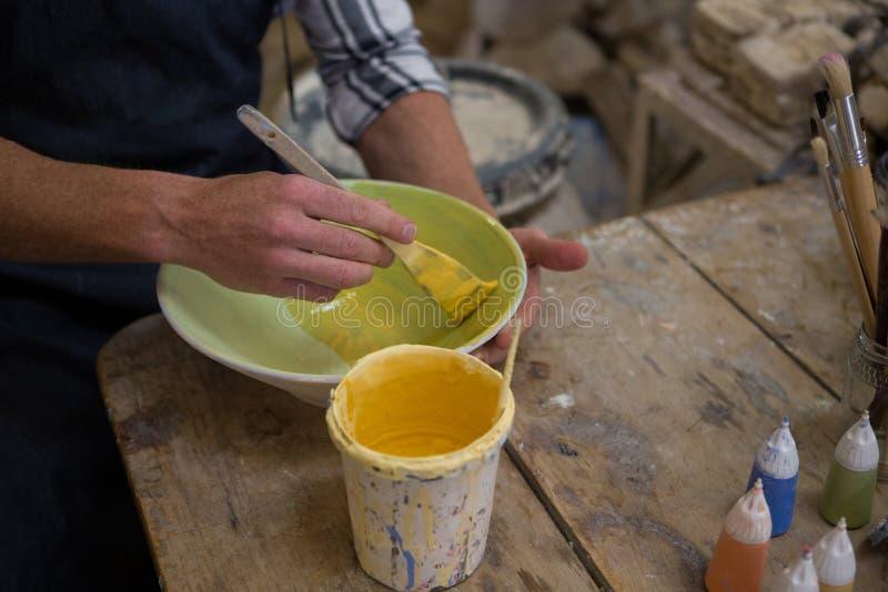 Οι αρσενικοί αγγειοπλάστες δίνουν τη ζωγραφική ενός κύπελλου στο εργαστήριο αγγειοπλαστικής στοκ φωτογραφίες