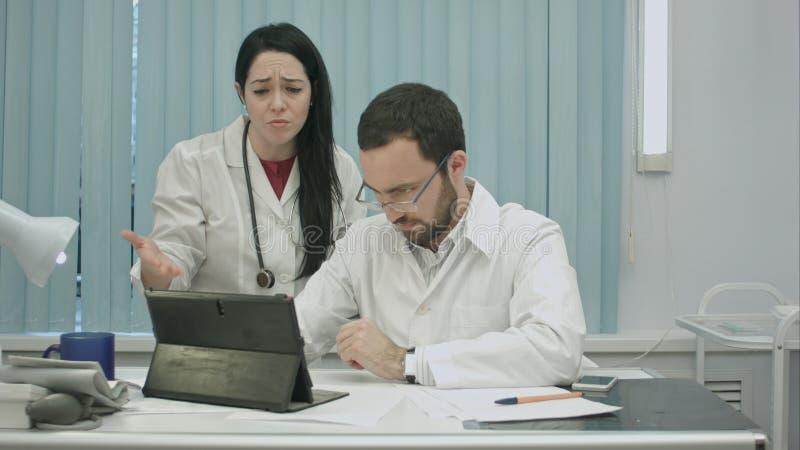 Οι αρσενικοί και θηλυκοί γιατροί συζητούν τα αποτελέσματα χρησιμοποιώντας την ταμπλέτα στοκ εικόνα
