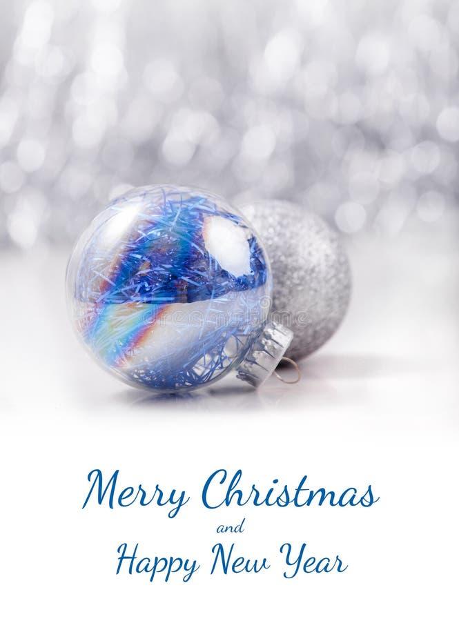 Οι ασημένιες και μπλε σφαίρες διακοσμήσεων Χριστουγέννων ακτινοβολούν επάνω bokeh υπόβαθρο με το διάστημα για το κείμενο Χριστούγ στοκ φωτογραφία