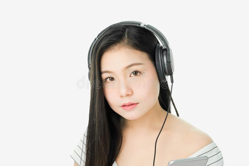Οι ασιατικές γυναίκες ακούνε τη μουσική από τα μαύρα ακουστικά στοκ φωτογραφία με δικαίωμα ελεύθερης χρήσης