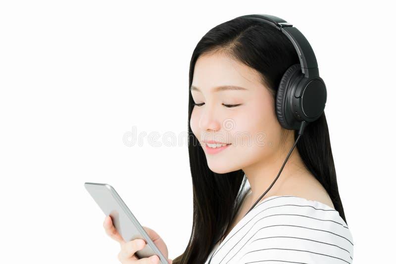 Οι ασιατικές γυναίκες ακούνε τη μουσική από τα μαύρα ακουστικά στοκ φωτογραφία