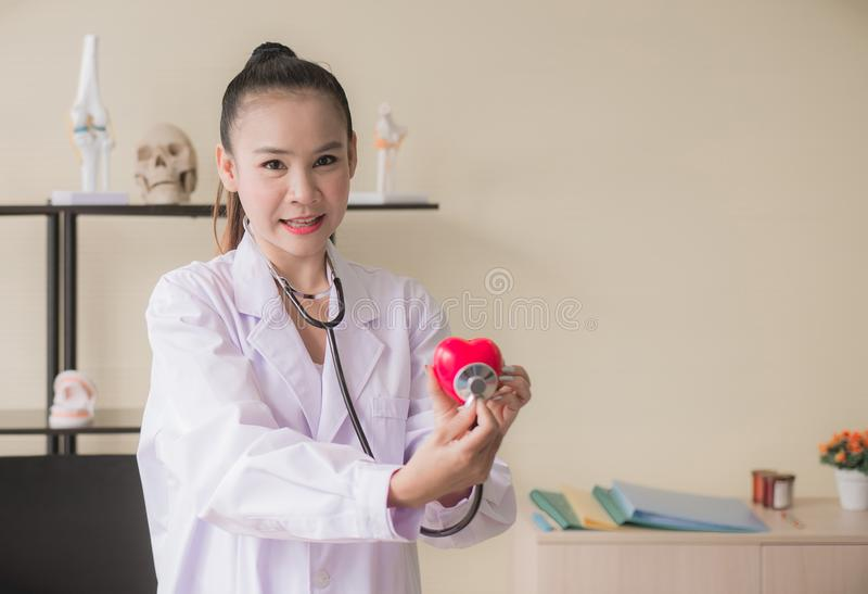 Οι ασιατικές γυναίκες γιατρών δίνουν την παρουσίαση στη θολωμένη καρδιά οργάνων κόκκινοι πρότυπου, ευτυχούς και το χαμόγελο, εκλε στοκ φωτογραφίες
