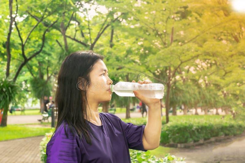 Οι ασιατικές γυναίκες είναι πόσιμο νερό από τα μπουκάλια στοκ φωτογραφία