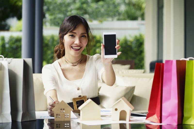 Οι ασιατικές γυναίκες χρησιμοποιούν το smartphone για να αντιπροσωπεύσουν την εγχώρια ακίνητη περιουσία π πώλησης στοκ φωτογραφία