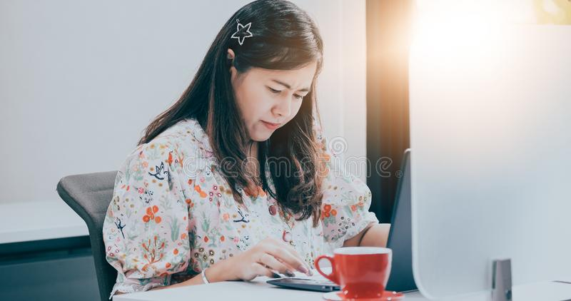 Οι ασιατικές επιχειρησιακές γυναίκες που χρησιμοποιούν το σημειωματάριο για την εργασία και πίνουν τον καφέ στοκ φωτογραφία