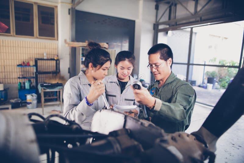 Οι ασιατικοί άνδρες και οι μηχανικοί και οι τεχνικοί γυναικών επισκευάζουν airc στοκ εικόνα
