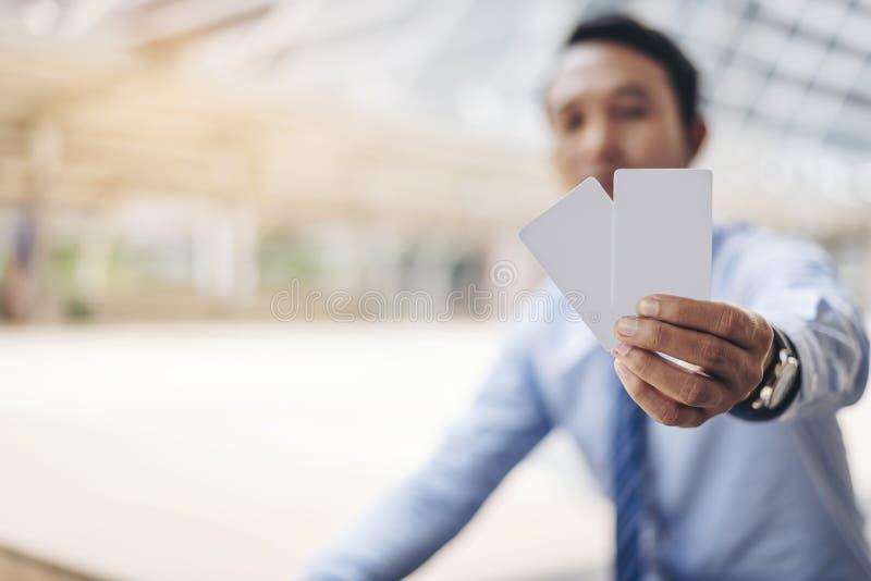 Οι ασιατικοί επιχειρηματίες κρατούν μια κενή κάρτα της τράπεζας που χρησιμοποιεί το ο στοκ εικόνα