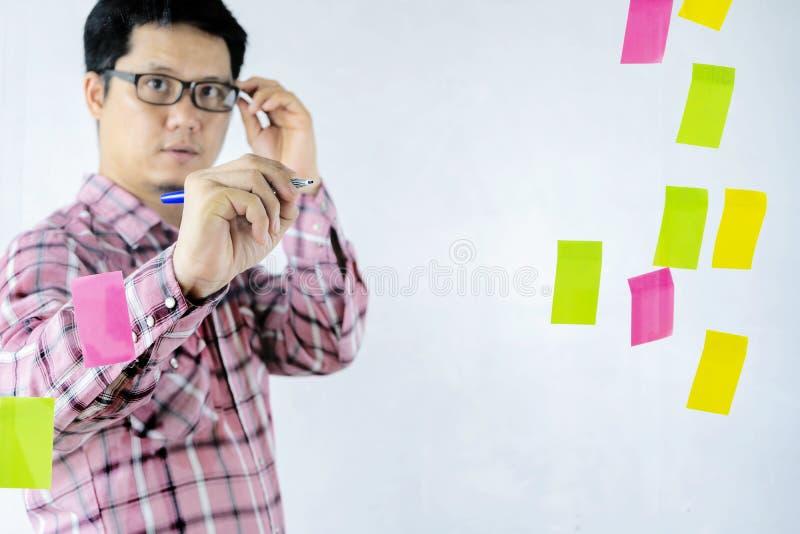 Οι ασιατικοί επιχειρηματίες μοιράζονται τις σκέψεις τους στον τοίχο γυαλιού στοκ εικόνα με δικαίωμα ελεύθερης χρήσης