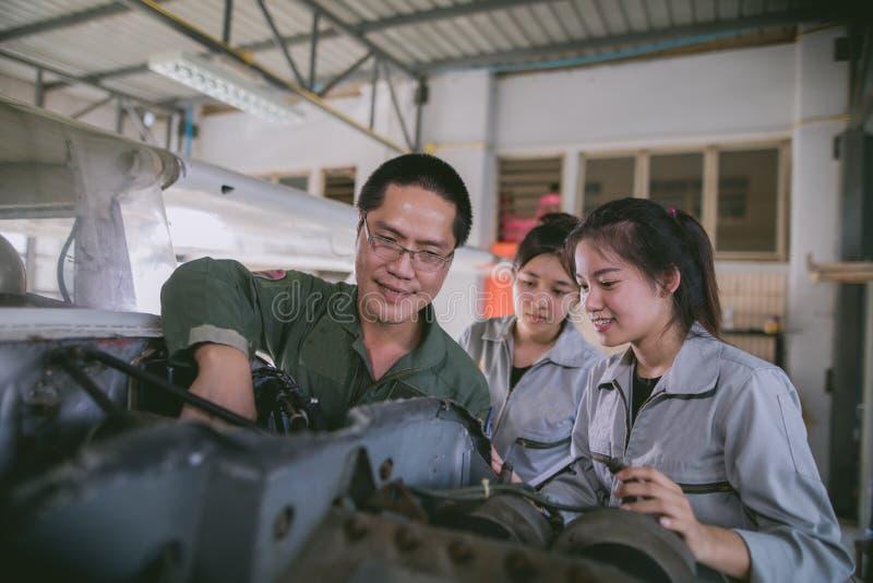 Οι ασιατικοί μηχανικοί και οι τεχνικοί σπουδαστών επισκευάζουν τα αεροσκάφη ο στοκ εικόνα