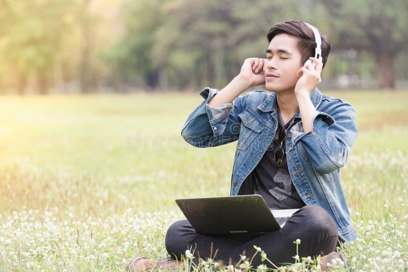 Οι ασιατικοί νεαροί άνδρες ακούνε τη μουσική στοκ φωτογραφία