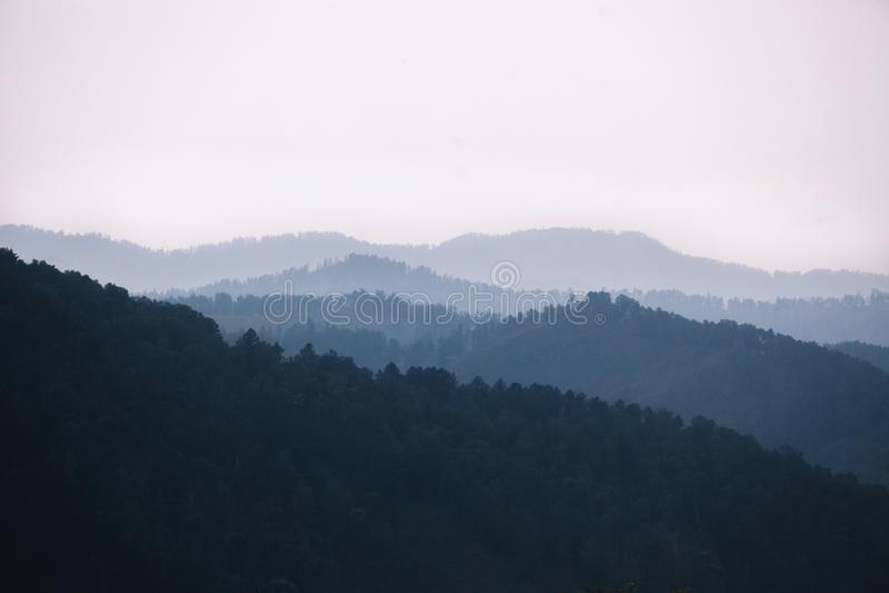 Ομίχλη που καλύπτει τα δάση βουνών Οι ατμοσφαιρικές σκιαγραφίες των βουνών στο μπλε χρώμα στοκ φωτογραφία με δικαίωμα ελεύθερης χρήσης