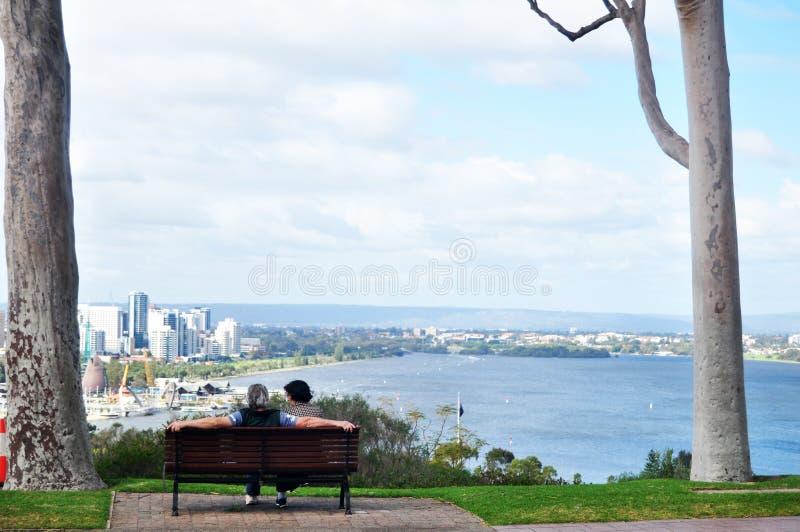 Οι αυστραλιανοί ηληκιωμένοι και οι ανώτερες γυναίκες ταξιδεύουν και κάθονται χαλαρώνουν στον πάγκο στον κήπο στο pe στοκ εικόνα