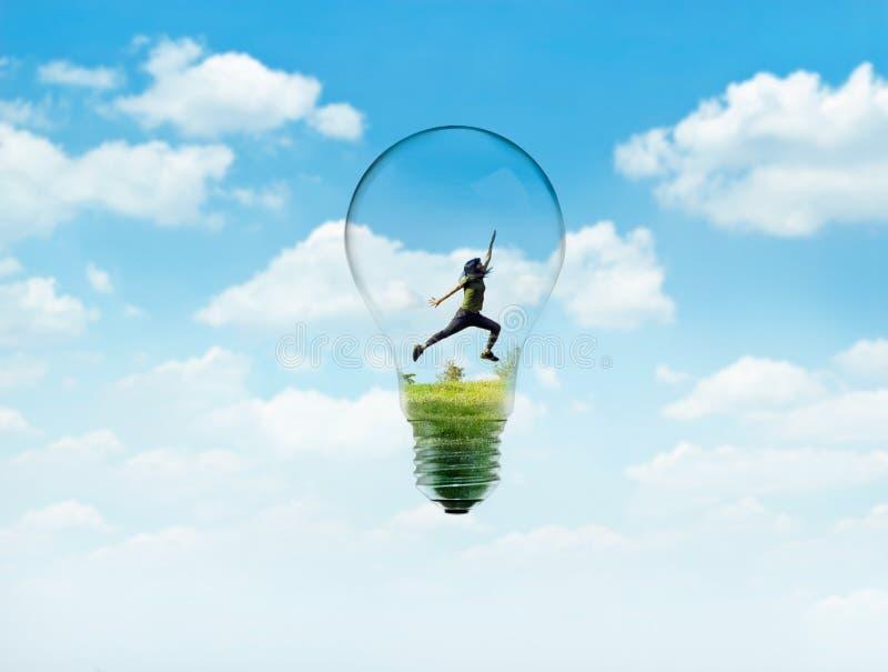 Οι αφηρημένες γυναίκες πηδούν στην πράσινη φύση στο φως βολβών με το μπλε ουρανό στοκ φωτογραφία