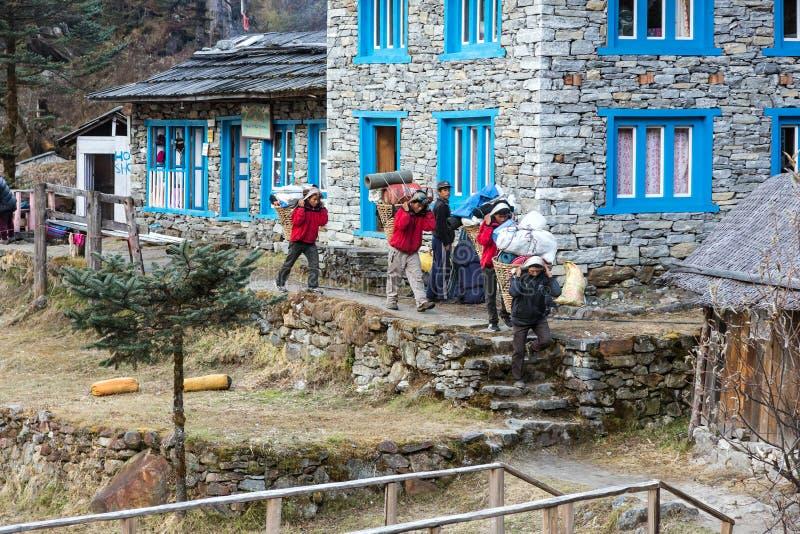 Οι αχθοφόροι της αποστολής βουνών του Ιμαλαίαυ που περπατούν ρίχνουν το χωριό στοκ εικόνες