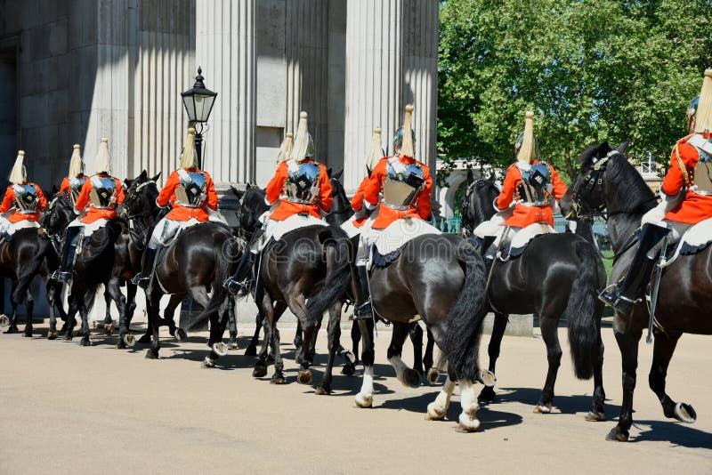 Οι βασιλικές φρουρές στην πλάτη αλόγου που ντύνεται στα εθιμοτυπικά κόκκινα παλτά περνούν σε μια παρέλαση - UK στοκ εικόνα
