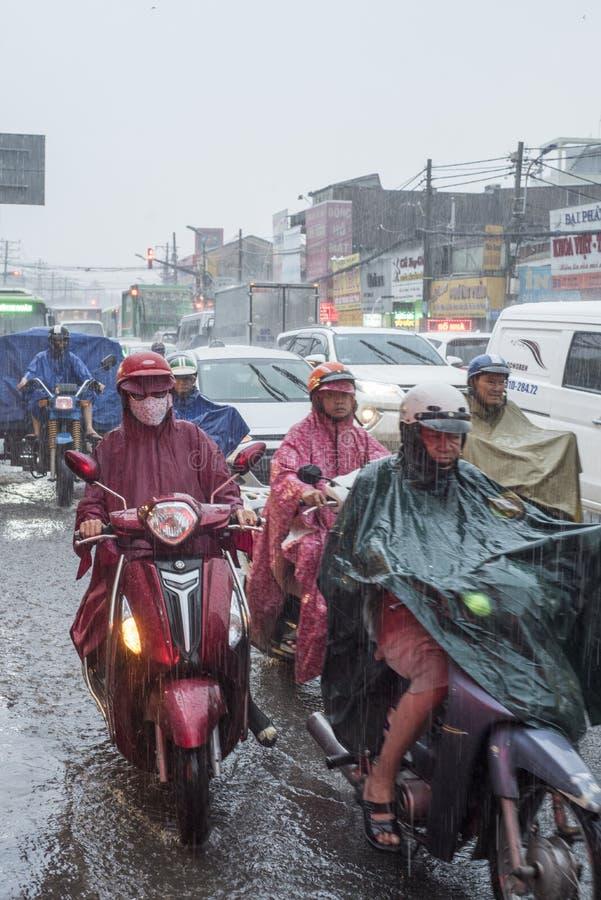 Οι βιετναμέζικοι αναβάτες κρατούν στη μετάβαση κάτω από τη βροχή σε μια οδό της πόλης Χο Τσι Μινχ, Βιετνάμ στοκ εικόνα με δικαίωμα ελεύθερης χρήσης