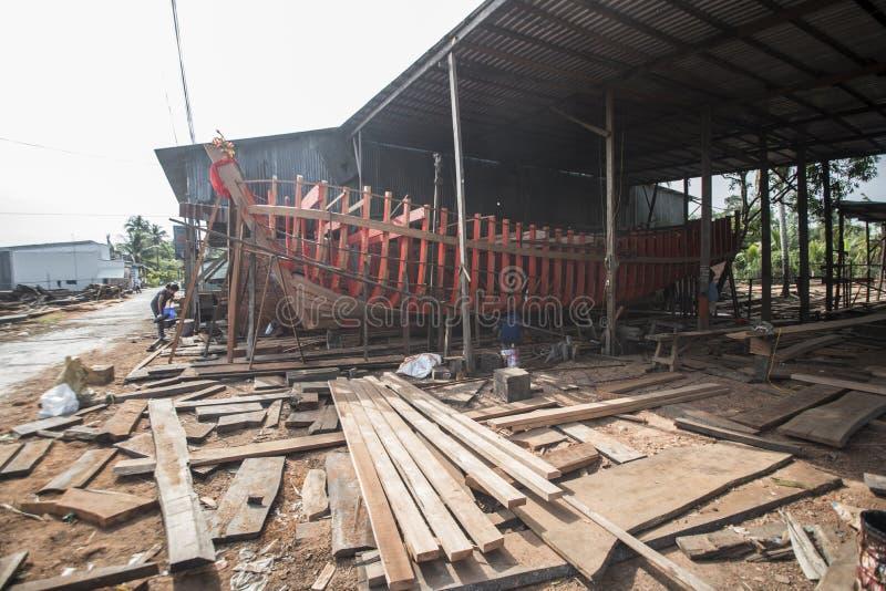 Οι βιετναμέζικοι εργαζόμενοι χτίζουν μια μεγάλη ξύλινη βάρκα στον κόλπο Nga στο νότιο Βιετνάμ στοκ φωτογραφία με δικαίωμα ελεύθερης χρήσης