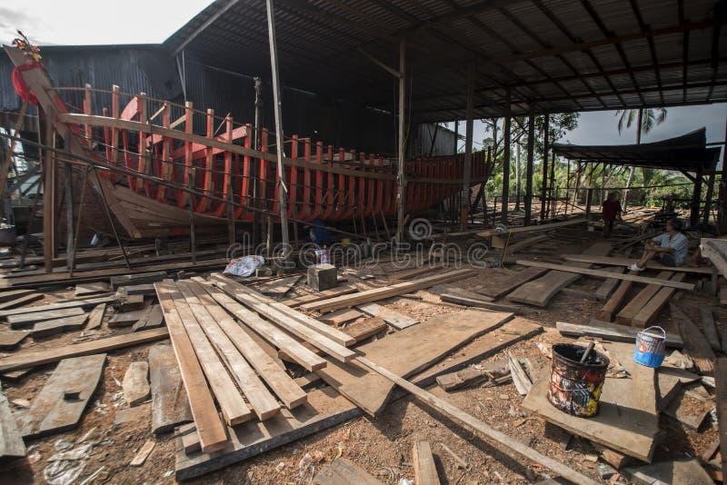 Οι βιετναμέζικοι εργαζόμενοι χτίζουν μια μεγάλη ξύλινη βάρκα στον κόλπο Nga στο νότιο Βιετνάμ στοκ εικόνα