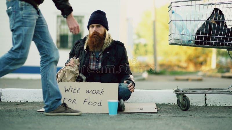 Οι βοήθειες νεαρών άνδρων στο άστεγο πρόσωπο και το δόσιμο του κάποιων χρημάτων ενώ οινόπνευμα ποτών επαιτών και κάθονται κοντά σ στοκ εικόνα με δικαίωμα ελεύθερης χρήσης