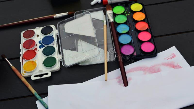 Οι βούρτσες και τα χρώματα των φωτεινών χρωμάτων με το έγγραφο είναι στον πίνακα στοκ φωτογραφίες με δικαίωμα ελεύθερης χρήσης