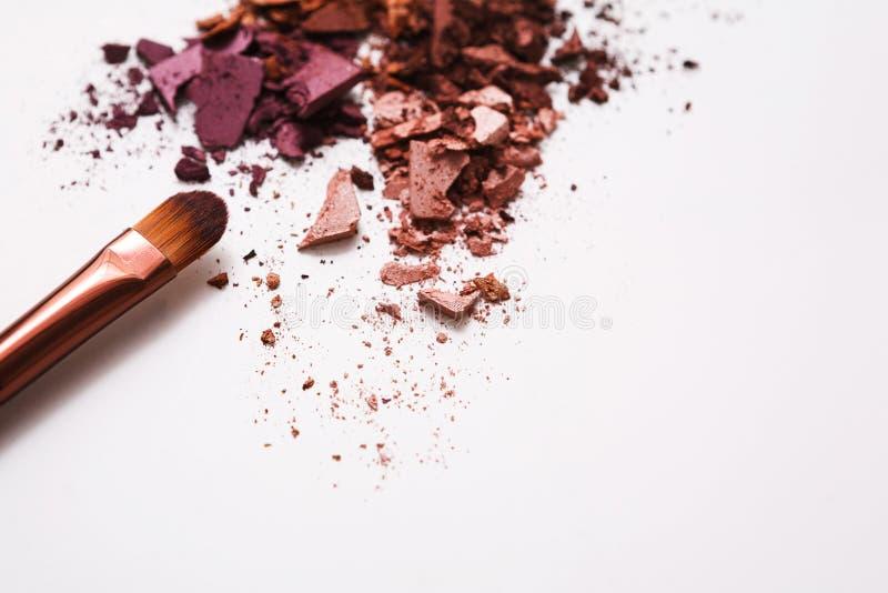 Οι βούρτσες Makeup με κοκκινίζουν ή σκιά ματιών του ροζ, του κοκκίνου και των τόνων κοραλλιών που ψεκάζονται στο άσπρο υπόβαθρο στοκ φωτογραφία