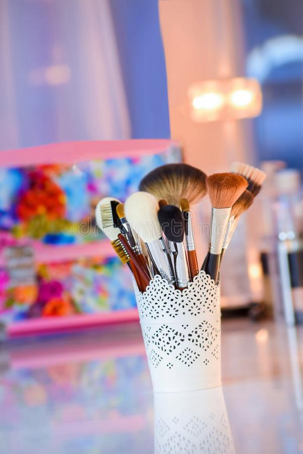 Οι βούρτσες Makeup που τέθηκαν στο μεταλλικό γυαλί στον άσπρο πίνακα στο χρώμα θόλωσαν το υπόβαθρο στοκ εικόνα