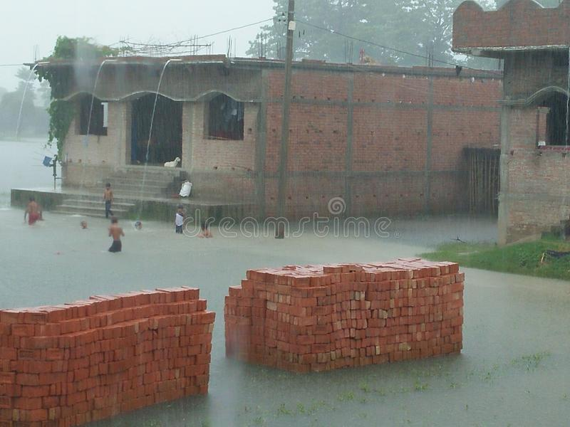 Οι βροχοπτώσεις απολαμβάνουν μέσα είναι τα παιδιά χωρικών στοκ εικόνα με δικαίωμα ελεύθερης χρήσης