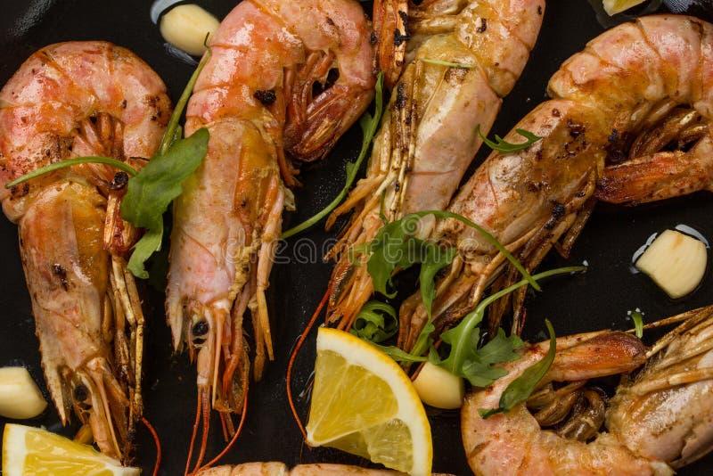Οι γαρίδες γαρίδων με το σκόρδο, το λεμόνι, τα καρυκεύματα και τον ιταλικό μαϊντανό διακοσμούν σε ένα μαύρο τηγάνι χρωματισμένη σ στοκ φωτογραφία με δικαίωμα ελεύθερης χρήσης